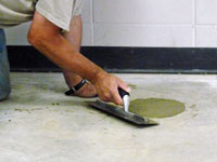 Repairing the cored holes in the concrete slab floor with fresh concrete and cleaning up the Fernley home.