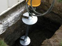 Installing a helical pier system in the earth around a foundation in Sparks